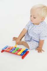 Baby boy playing with a xylophone
