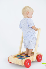 Baby boy playing with a push cart