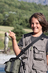 jeune garçon pêcheur exhibant sa truite avec fierté