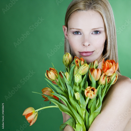A young blonde woman holding a bunch of orange tulips