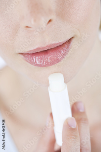 A young woman applying lip balm, close-up