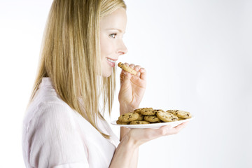 A young blonde woman eating a cookie, side view