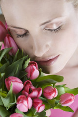 A young woman holding a bunch of pink tulips, close-up
