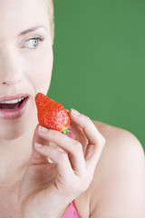 A young woman eating a strawberry, close-up
