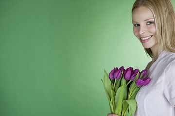 A young blonde woman holding a bunch of purple tulips, smiling