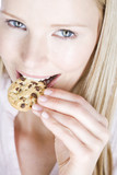 A young woman eating a cookie, looking up