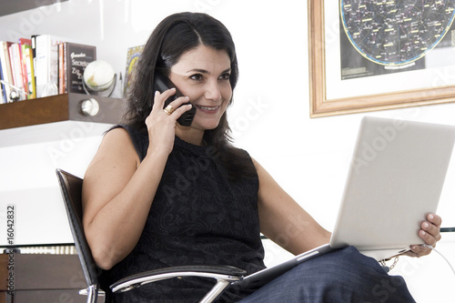 Woman working with phone and laptop