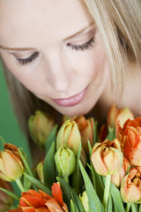 A young woman looking at a bunch of orange tulips, looking down