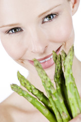 A young blonde woman holding a bunch of asparagus, close-up