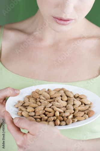 A young woman holding a plate of almonds