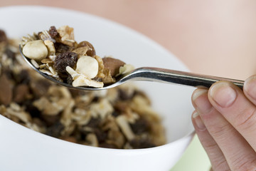 A woman holding a bowl of muesli, close-up