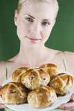 A young woman holding a plate of hot cross buns