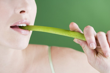 A young woman eating a stick of celery, close-up