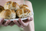 A young woman holding a plate of hot cross buns, close-up