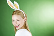 A young blonde woman wearing rabbit ears, winking