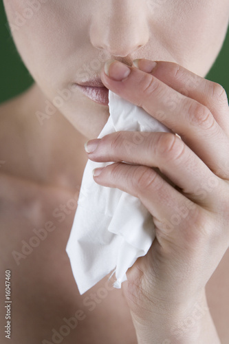 A young woman holding a tissue, close-up
