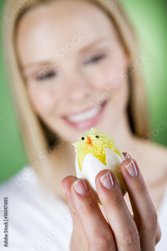 A young woman looking at an Easter chick toy, close-up
