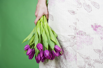 A woman holding a bunch of purple tulips by her side, close-up