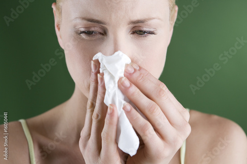 A portrait of a young woman blowing her nose