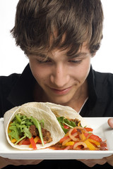Young man smelling plate of fresh tacos