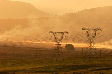 Backlit power pylons in mist at sunset