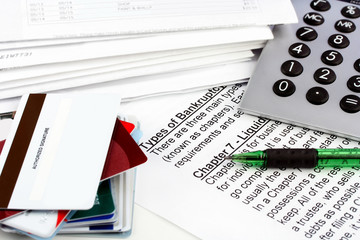 Bankruptcy document with bills, credit cards, calculator and pen