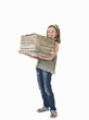 Pretty, young girl holding pile of old newspapers for recycling