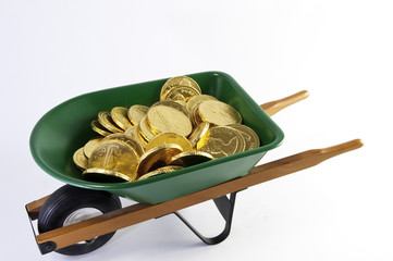 Gold coins top view in wheel barrel