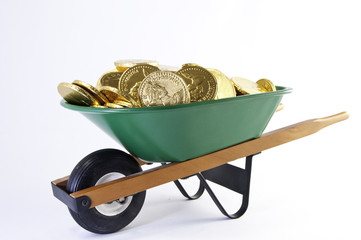 Gold coins in wheel barrel
