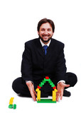 Young mane wearing suit is making a house with cubes toys poster
