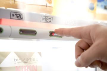 自販機で飲物を買う男性