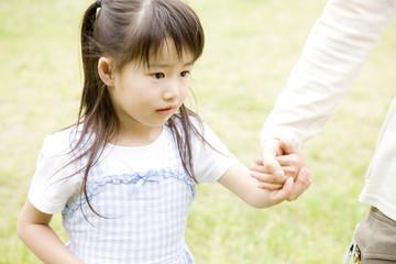 母親と手を繋いで歩く女の子