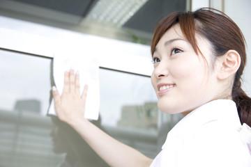 窓ガラスを拭く女性店員