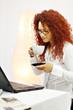 Frau trinkt Kaffee am Arbeitsplatz