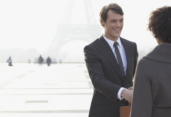 Two businesspeople outdoors shaking hands by Eiffel Tower