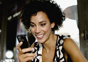 Woman in restaurant using cellular phone