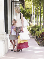Woman and young girl outdoors with shopping bags window shopping