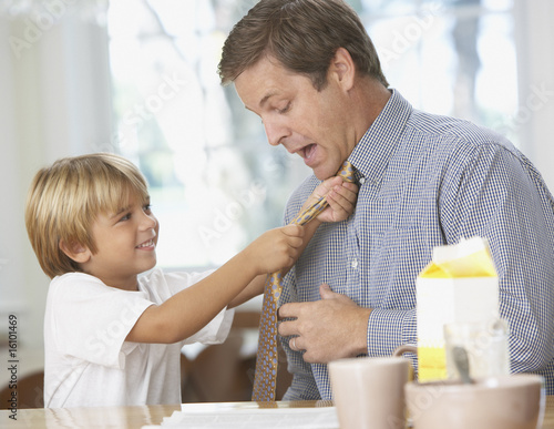 Young boy tightening man's necktie in kitchen