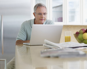 Man in kitchen using laptop