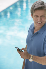 Man outdoors holding a mobile phone by a swimming pool