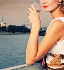 Beautiful woman drinks chamlagne near the river