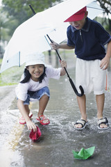 Two young kids outdoors in rain playing with paper boats