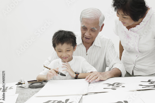 Couple and young boy indoors painting Chinese letters