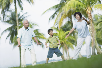 Couple outdoors in park with young boy doing tai chi