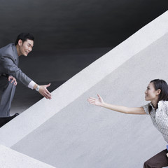 Businessman helping businesswoman over structure outdoors