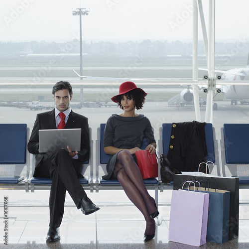 Businessman with laptop in airport beside woman with shopping bags