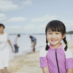 Young girl outdoors at beach with people in background
