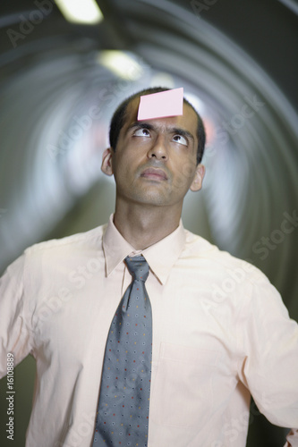Businessman in corridor with post-it stuck to forehead