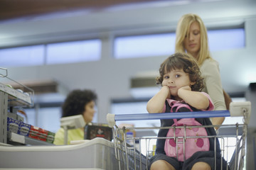Young girl in grocery store with woman at check-out