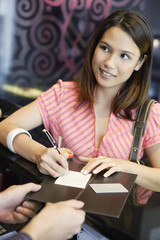 Woman in restaurant signing check